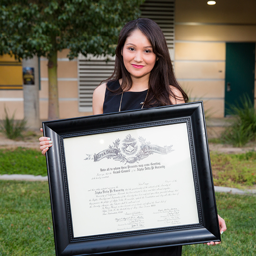 sorority woman posing with installation certificate