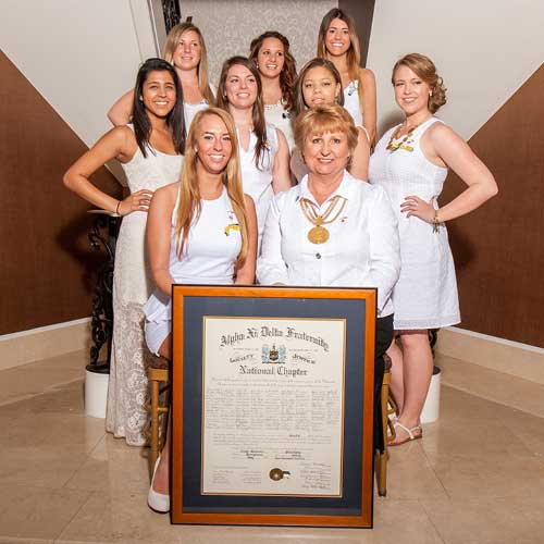 sorority women posing for installation photography with certificate